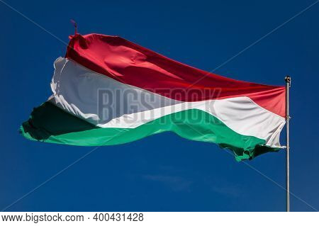 Hungarian Striped Flag Waving In Strong Wind Against The Blue Sky