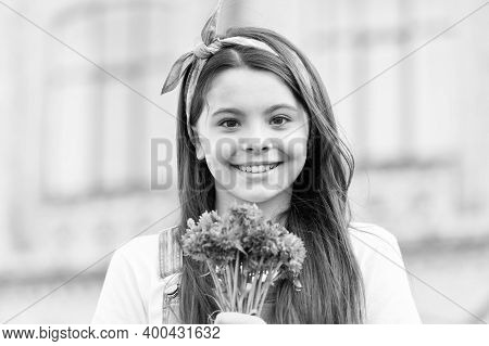 Blossom Into A New You. Happy Girl Hold Flowers Outdoors. Beauty Look Of Little Child. Beauty Salon.