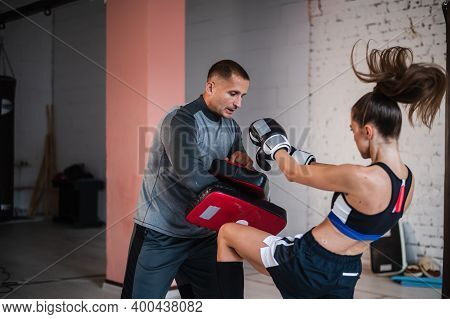 A Young Strong Kickboxer Girl Kicks Her Sparring Partner With A Boxing Paw In A Personal Training Se
