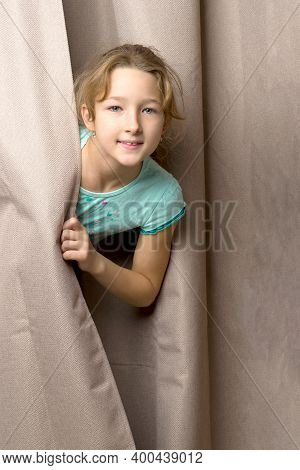 Pretty Teen Girl Peeping From Behind Curtains. Portrait Of Smiling Playful Teenager Looking Through