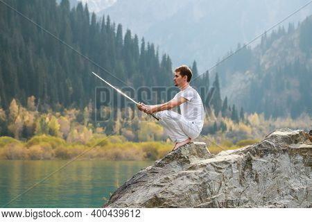 A Wise Man Sits On A Stone And Holds A Sword In His Hands. Mountain Lake Background.