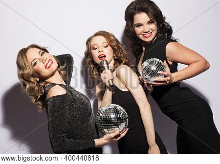Three charming ladies dressed in black cocktail dresses singing with a microphone, holding disco balls and smiling. Over white background.