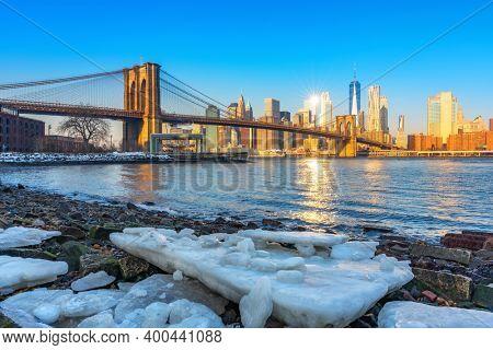 Brooklyn bridge East river and Manhattan at winter sunrise, New York City
