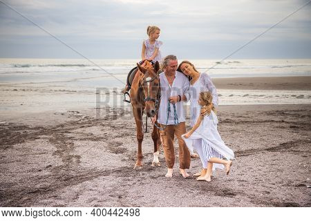 Horse Riding. Little Pretty Girl On A Horse. Father Leading Horse By Its Rein. Mother Hugging Daught