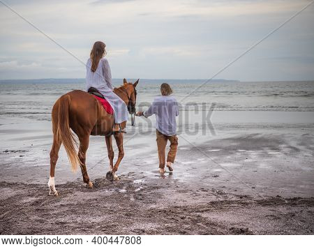 Horse Riding By The Sea. Woman On A Horse. Man Leading Horse By Its Reins. Love To Animals. Husband