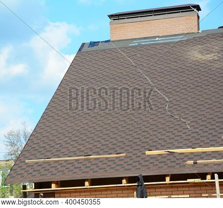 A View On An Incomplete Roof With Asphalt Shingles Installation On The Waterproof Underlayment. Asph