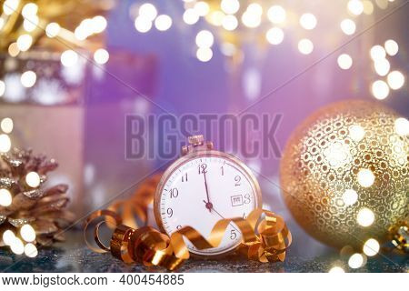 Old golden clock close to midnight, champagne and sparkling Christmas decoration - New Year concept