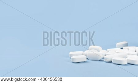 Medical Banner Of Many White Capsule Tablets Or Pills On Blue Table. Close Up. Healthcare Pharmacy A