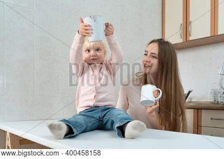 Small Child In Surprise Looks At Mug Sitting Next To Mom In Kitchen.