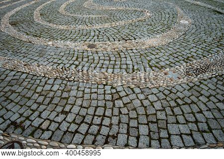 Tangled Decorative Path Made With Pebbles On The Stone Pavement. Background Of Decorative Cobbleston