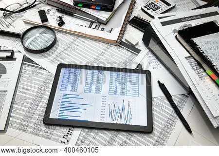 business office desk closeup - tablet computer with tables and graphs on the screen, financial reports, analysis and accounting, set of documents for bookkeeping