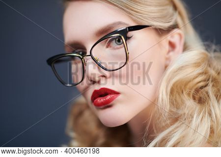 Business style. Close-up portrait of a fashionable blonde woman in elegant glasses. Optics, eyewear.