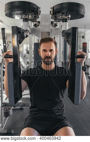 Man Working Hard At The Gym. Pectoral Muscles Exercises With Training Weight Machine Station In Gym.