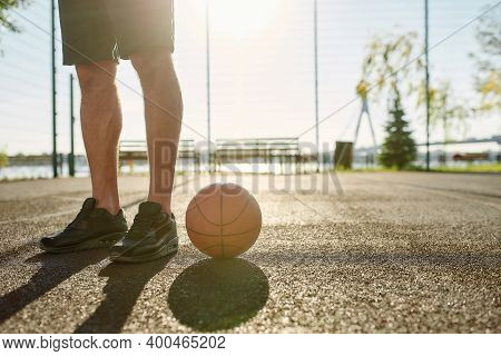 Close Up Of Legs Of Young Male Basketball Player In Sportswear Standing On The Court With Basketball