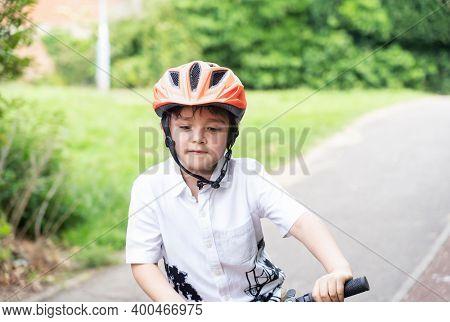 Avtive Kid Wearing A Bike Helmet, Outdoors Portrait Happy Kid With Smiling Face Wearing A Cycling He