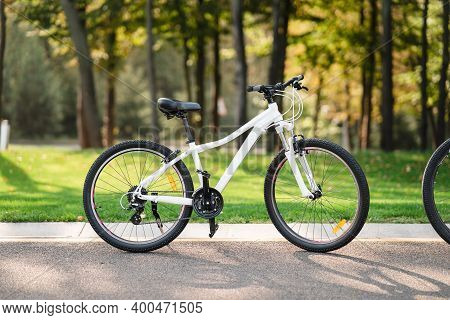 White Bicycle Standing In Park. Morning Fitness, Loneliness.