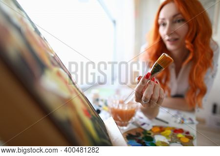 Close-up Of Woman Holding Natural Paintbrush. Beautiful Red Haired Artist Painting On Canvas At Home