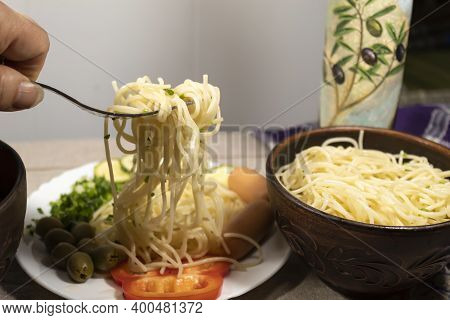 On The Table Is A Bowl Of Spaghetti And A White Plate With Spaghetti, Sausages, Peppers, Olives And