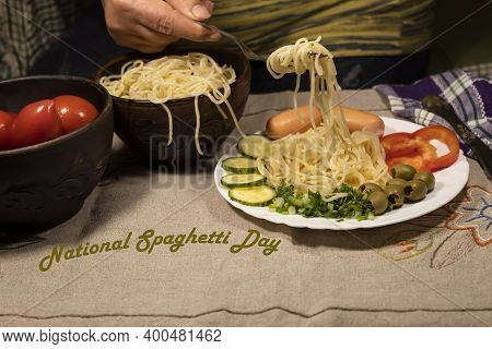 There Is Food On The Table. On The Plate Is Spaghetti, Sausages, Peppers, Olives, Cucumber. The Hand