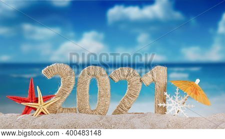 Concept Of Celebrating The New Year In Hot Countries. The Inscription 2021 In The Sand And A Snowfla
