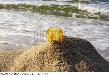 Amber On A Sandy Beach. One Piece Of Transparent Mineral Sunstone On The Background Of The Sea. Anci