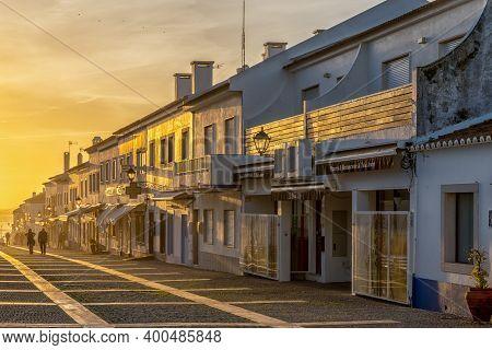 Porto Covo, Portugal - 20 December 2020: People Enjoying An Evening Walk On The Rua Vasco Da Gama In