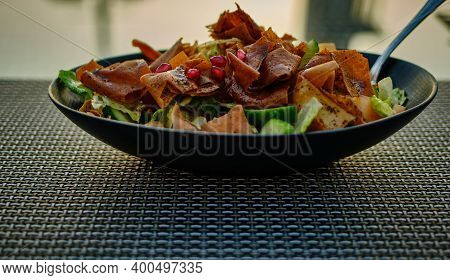 Fattoush (lebanese Salad) Close Up  Image In A Black Plate With Blurred Background. It Is Made With