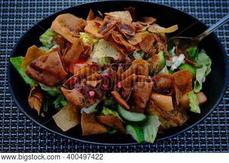Fattoush (lebanese Salad) Close Up  Image In A Black Plate . It Is Made With Vegetables And Crispy T