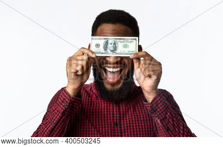 Easy Money. Happy Black Man Holding One Hundred Dollar Banknote In Front Of Face Posing On White Stu