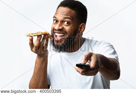 Black Man Eating Pizza And Watching Tv Pointing Remote Control To Camera Posing Over White Studio Ba