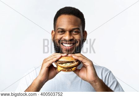 Junk Food Eater. Cheerful African Man Holding Burger Smiling To Camera Standing On White Background