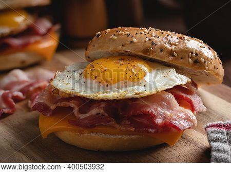 Closeup Of A Breakfast Bagel Sandwich With Fried Egg, Bacon And Cheese On A Wooden Cutting Board