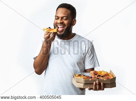 Fast Food. Hungry Black Guy Eating Pizza Enjoying Junk Food Holding Box Standing In Studio Over Whit