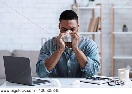 Sick Black Guy Working In Office, Sitting At Laptop And Blowing Nose In Paper Napkin Indoors. Ill Em