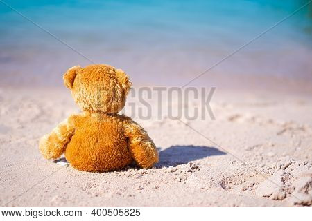 Broken Heart Or Loneliness Concept. Alone Teddy Bear Sitting On Sand Beach With Blue Sea. Symbol For