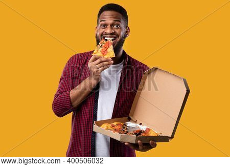 Happy African Man Eating Pizza Smiling To Camera Standing Over Yellow Studio Background. Junk Food E
