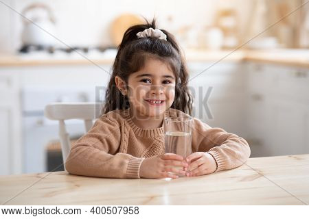 Healthy Liquid. Portrait Of Cute Little Girl Sitting In Kitchen Holding Glass Of Water, Pretty Child