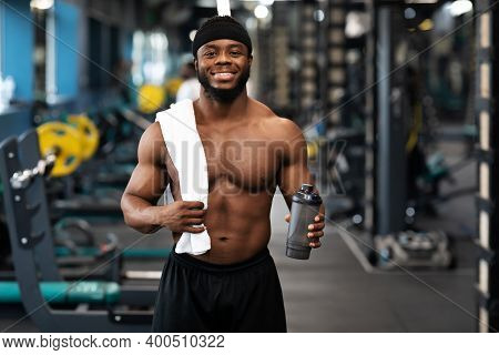 Rest After Workout. Happy African American Bodybuilder Holding Water Or Protein And Towel At Gym, Em