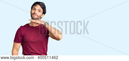 Handsome hispanic man wearing casual clothes cutting throat with hand as knife, threaten aggression with furious violence