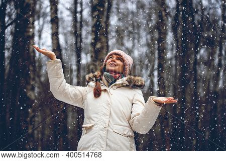 Young Woman In A Winter Park In Snowfall. Woman Having Fun On Winter Nature. Winter Portrait Of Funn