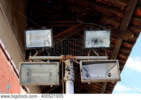 Set Of Four Old Floodlights Mounted On Metal Post. Lighting Support At The Railway Station.