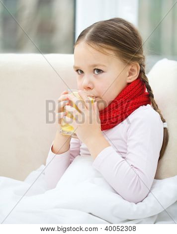 Ill little girl is drinking vitamin cocktail while sitting on a sofa