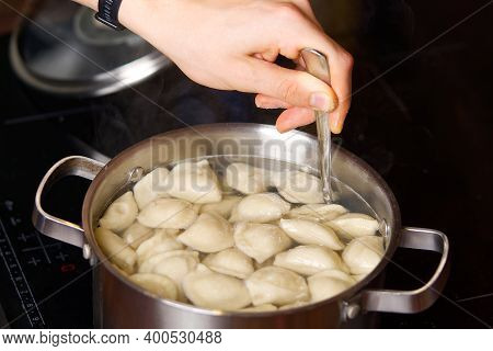 The Cook Mixes The Dumplings With A Spoon In A Pot Of Boiling Water. Boiled Dumplings In A Pan