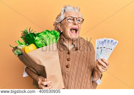 Senior grey-haired woman holding groceries and colombian pesos banknotes angry and mad screaming frustrated and furious, shouting with anger. rage and aggressive concept.