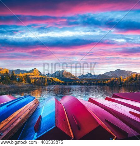 Picturesque autumn view of lake Strbske pleso in High Tatras National Park, Slovakia. Row of red wooden boats and high mountains on background. Landscape photography