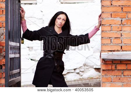 Sexy Woman Stands Near The Brick Wall