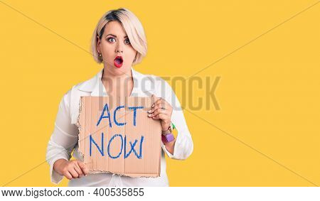 Young blonde plus size woman holding act now cardboard banner scared and amazed with open mouth for surprise, disbelief face