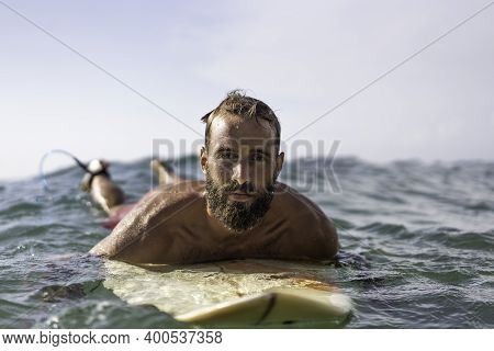 Young Hipster Man Swimming On The Surfboard Into The Sea Water Waiting For A Big Wave - Cool Guy Hav