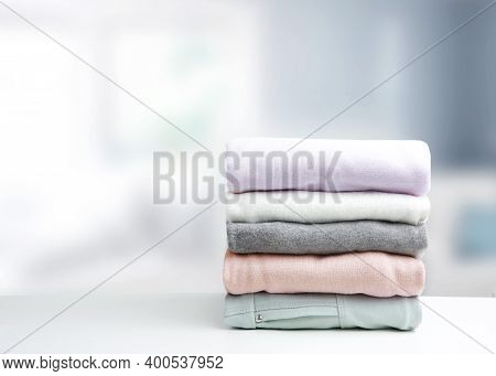 Soft Colors Stack Of Clothing,clothes Folded On Table Empty Copy Space Background.colorful Garment S