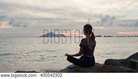 Woman do yoga and sit beside the sea